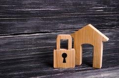 Trähus med en hänglås Hus med ett lås Säkerhet och säkerhet, säkerhetsåtgärd, lån för en inteckna BESLAG AV EGENSKAPEN arkivbilder