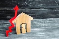 Trähus med en man inom pilred upp begrepp av den höga begäran för fastighet öka energieffektivitet av hus stigning arkivbild