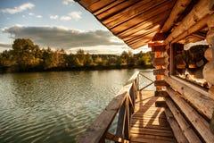 Trähus med en terrass på vattnet på sjön, på solnedgången, Arkivbild