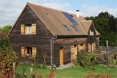 Trähus med solpaneler och slutare Royaltyfria Bilder