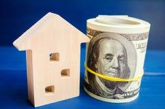 Trähus och dollar på en blå bakgrund verkligt begreppsgods köpa sälja som hyr kreditering för egenskap försäljningsapartme royaltyfri fotografi