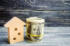 Trähus och dollar på en blå bakgrund verkligt begreppsgods köpa sälja som hyr kreditering för egenskap försäljningsapartme royaltyfri bild
