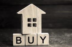 Trähus och inskriften 'köp 'på träkvarter Begreppet av köpandeegenskapen Inhandla ett hem, lägenheten, fastighet arkivfoto
