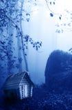Trähus och mystiskt landskap av den dimmiga skogen Royaltyfri Fotografi