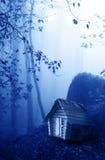 Trähus och mystiskt landskap av den dimmiga skogen Royaltyfri Bild