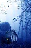 Trähus och mystiskt landskap av den dimmiga skogen Arkivfoton
