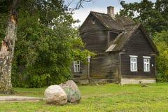 Trähus och stenblock Arkivfoto