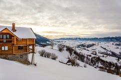 Trähus på en berglutning i snöblåttjul som är hhory av Royaltyfri Foto