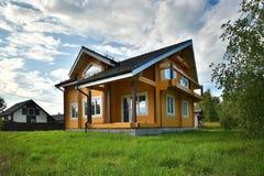 Trähus på grönt gräs med blå himmel Royaltyfria Bilder