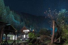 Trähus på natten arkivbild