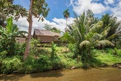 Trähus på styltor med gömma i handflatan på flodstrand i indonesia arkivbild