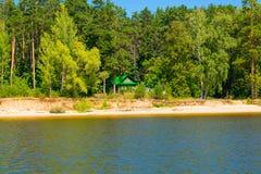 Trähuset kikar ut ur pinjeskogen på banken om den varma soliga dagen för floden Arkivbild
