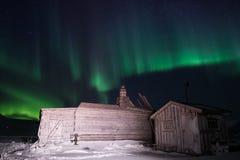 Trähuset, yurt förlägga i barack på bakgrunden som det polara nordliga norrskenet tänder Arkivfoton