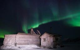 Trähuset, yurt förlägga i barack på bakgrunden som det polara nordliga norrskenet tänder Arkivbild