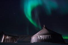 Trähuset, yurt förlägga i barack på bakgrunden som det polara nordliga norrskenet tänder Fotografering för Bildbyråer