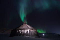 Trähuset, yurt förlägga i barack på bakgrunden som det polara nordliga norrskenet tänder Royaltyfri Bild