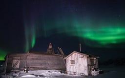 Trähuset, yurt förlägga i barack på bakgrunden som det polara nordliga norrskenet tänder Royaltyfri Fotografi