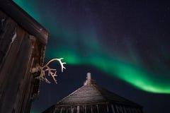 Trähuset, yurt förlägga i barack på bakgrunden som det polara nordliga norrskenet tänder Royaltyfri Foto