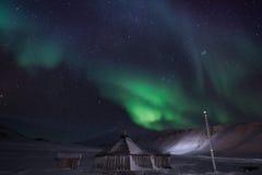 Trähuset, yurt förlägga i barack på bakgrunden som det polara nordliga norrskenet tänder Arkivbilder