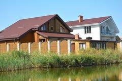 Trähuskonstruktion med metalltaket på flodbanken royaltyfri foto