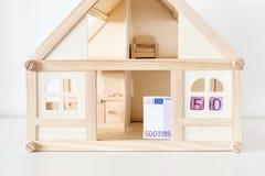 Trähusmodell med räkningen för euro 500 Hushyra och försäljning Kostnader och kostnader för husatt behandla Husbesparingbegrepp C Royaltyfri Fotografi