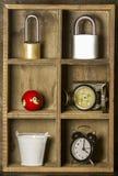 Trähylla och klocka, lås, kompass, hink arkivbilder