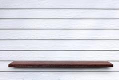 Trähylla på den vita syntetiska wood väggen arkivfoto
