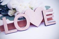 Träinskrift för förälskelsebokstäver med hjärtaform Tappningstil med vita blommor tonat Royaltyfria Bilder