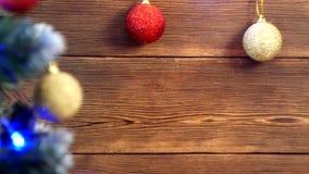 Träjulbakgrund med julbollar av olika färger och en julgran på som julljusen arkivfilmer