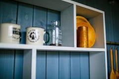 Träkökhylla på den blåa träväggen Genomskinligt kaffe lurar royaltyfria foton