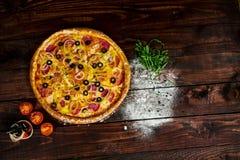 Träköksbord med pizza som strilas med mjöl arkivbilder