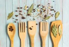 Träköksgeråd och olika kryddor på Royaltyfri Foto