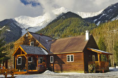 Träkabin bland snöig berg royaltyfri foto
