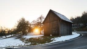 Träkabin i solnedgången, vinter med den mörka gatan framtill av sikten, snö Arkivfoto
