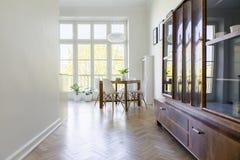 Träkabinett i ljus matsalinre med vita stolar Royaltyfria Bilder