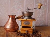 Träkaffekvarn och cezve på tabellen royaltyfri fotografi