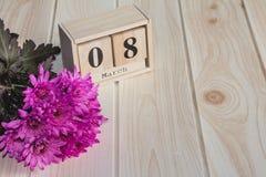 Träkalender för mars 8, bredvid purpurfärgade blommor på trätabellen Royaltyfria Bilder