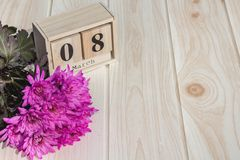 Träkalender för mars 8, bredvid purpurfärgade blommor på trätabellen Royaltyfri Fotografi