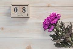 Träkalender för mars 8, bredvid purpurfärgade blommor på trätabellen Arkivfoton