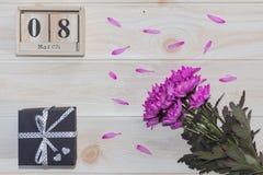 Träkalender för mars 8, bredvid purpurfärgade blommor på trätabellen Royaltyfri Bild