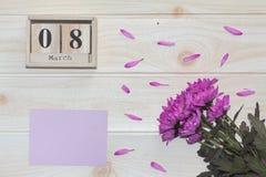 Träkalender för mars 8, bredvid purpurfärgade blommor på trätabellen Royaltyfri Foto