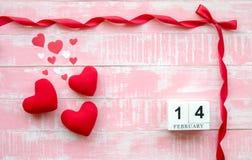 Träkalendern 14 Februari består av ett rött band och en hjärta förlagd sida - vid - sidan med en röd bakgrund valentin för dag s royaltyfria bilder