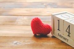 Träkalendern på Februari 14, röd hjärta var den förlade sidan - vid - sidan med gammal träbakgrund arkivbild