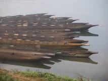 Träkanot på floden dimmig morgon Arkivfoto