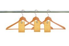 Träklädhängare med tomma etiketter som isoleras på vit Arkivbild