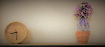 Träklockan med blomkrukan och varnar soluppsättningen royaltyfria bilder