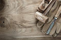 Träklubba som rakar skyddande handskar för plan stämjärn på den wood boaen royaltyfri fotografi