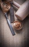 Träklubban som krullas upp stämjärn för shavings på det wood brädet, lurar framlänges Arkivfoto