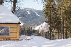 Träkoja i en bergskog i vinter Arkivfoton