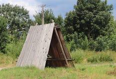 Träkoja i gräsplanen för en ferie i vandringen Det primitiva skyddet av regn och solen för spanar, jägare och herdar Romans av royaltyfria bilder